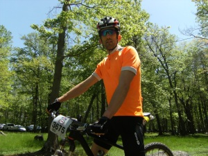 Alex on his bike in an orange jersey.