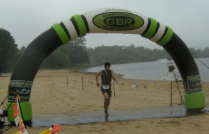 Alex running under the inflatable Green Brook Racing banner.