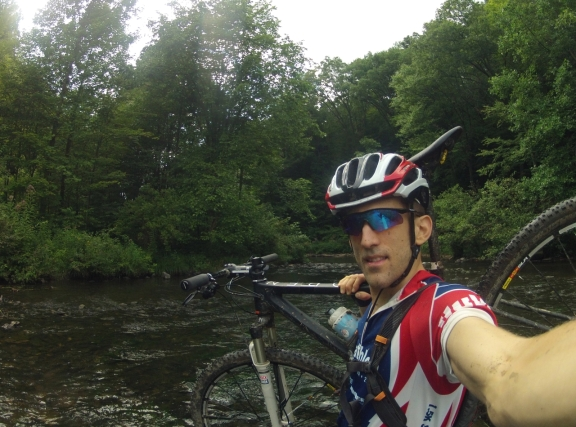 Creek/river crossing with Alex holding bike on his shoulder