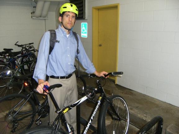 Alex parking his bike in a bike rack in a parking garage