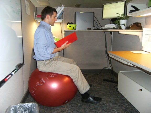 Alex sitting on a large exercise ball and reading from a binder