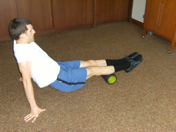 Alex rolling legs on trigger point roller