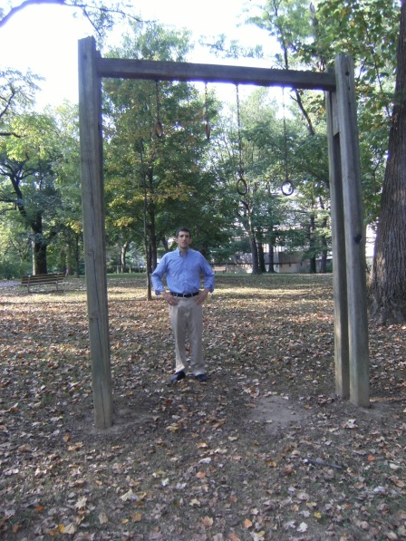 Alex standing on a playground below a set of rings