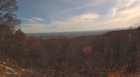 Partly cloudy sky and mostly barren trees in late fall, with a panaromic view of Fredrick below
