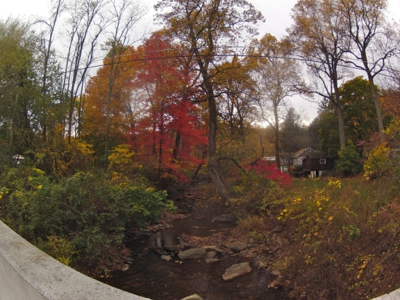 On a bridge overlooking a 20 ft wide, shallow creek littered with rocks, and trees with red and orange fall color as well as some green leaves and barren branches