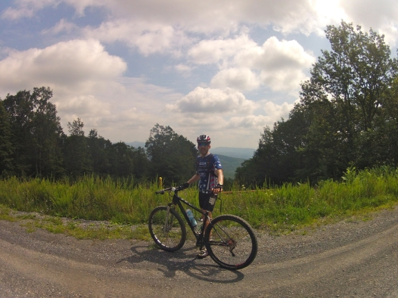 Standing beside my OPEN 29er on a gravel mountain road, beneath a bright partly coludy sky with views of the blue ridges of the Appalachian mountains in the background