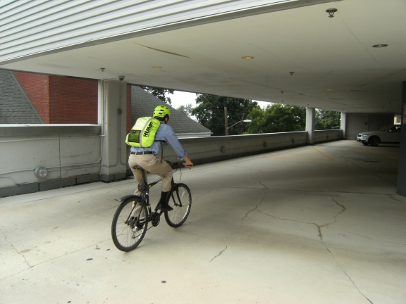 Picture of the author riding away on his bike with the highly visible bright yellow backpack cover facing the camera
