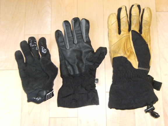 Three gloves lined up, on the left is a light pair, the middle is a thin pair of wind-resistance gloves, and on the right are thick, heavy duty winter gloves