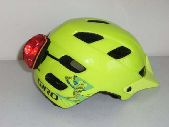 A bright green Giro Feature helmet with a red LED light attached to the back