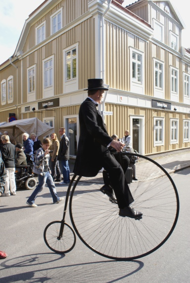 Picture of a man dressed in 19th Century British suit and top hat pedaling a penny-farthing bike along the main street of a small sweedish town