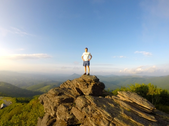 The author standing atop a rock outcropping near the peak of Snake mountain, with green rolling ridges fading into the blue sky overhead