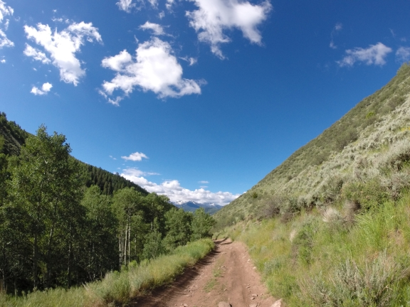 narrow dirt road with wild grass on each side between two ridges under a royal blue sky with sparce clouds