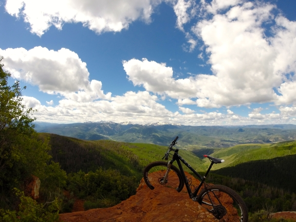 OPEN 29er mtb resting on red rocks, blue sky with some white clouds