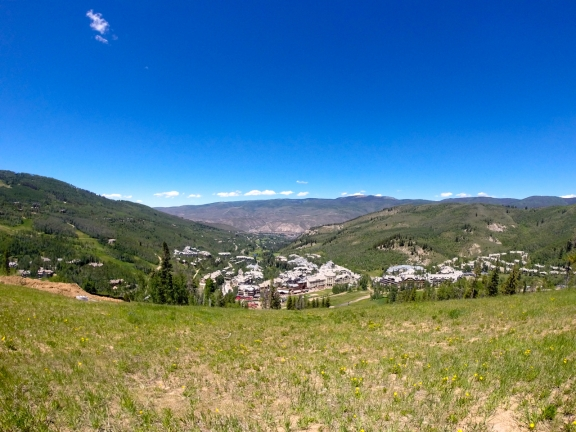 A grassy mountain plain under my feet, a pine covered mountain ridge to the left, the roofs of hotels and shops of Beaver Creek in the center, and the brown and green slopes of red and white mountain on the horizon under a cloudless magnificant blue sky