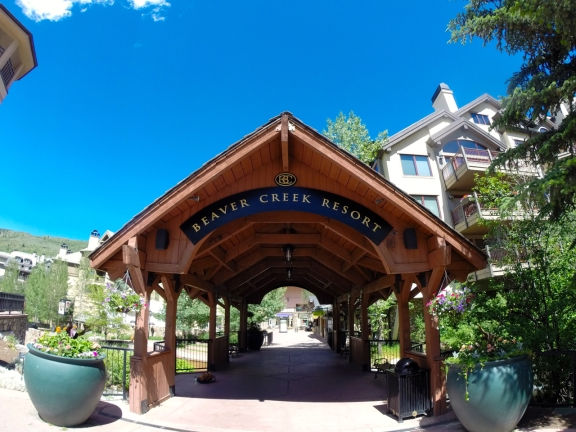 Wooden archway entrance to Beaver Creek Resort, blue sky overhead