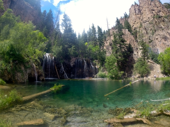 Turquoise lake fed by a several waterfalls, surrounded by tall pines and flanked by several hundred foot rock walls