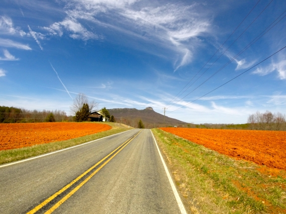 The distinctive red dirt of North Carolina and beautiful blue skies make the perfect backdrop for the unique prominence of Pilot Knob, towering above the Piedmont.