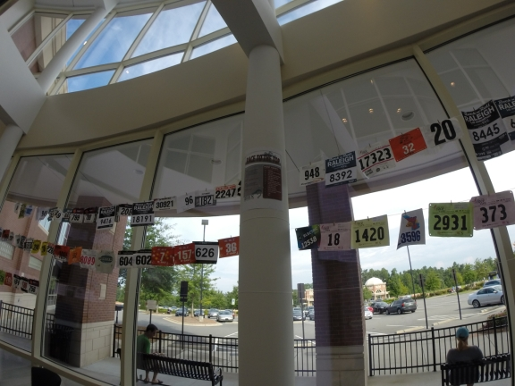 Banner of race bib numbers from dozens of athletes lining the wall at the Rex Wellness gym