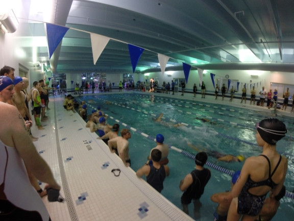 Racers line the sides of the pool, and inside on the far left edge, waiting their turn to start the five lap swim