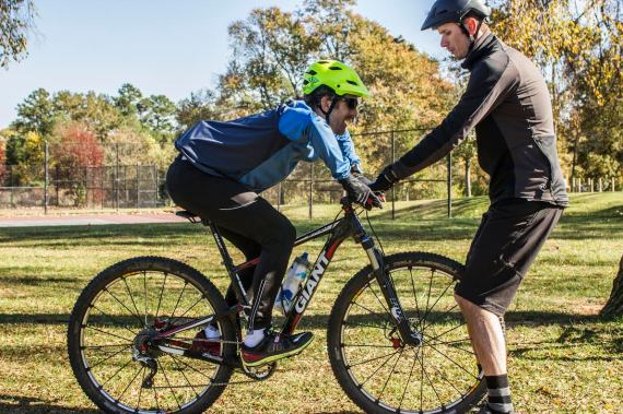 Instructor holding handlebars while student practices mountain biking attack position.