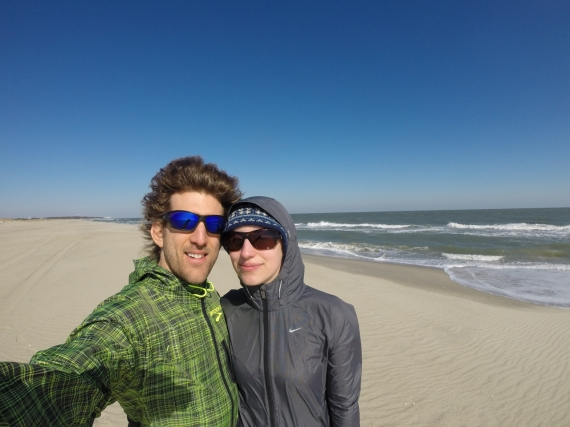 Couple, both in jackets and sunglasses, smiling for the camera with an empty beach in the background.