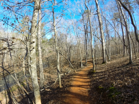 North Carolina red clay trail cut through forest along the bank of New Hope Creek.
