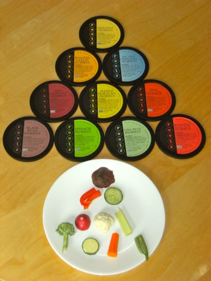 Pyramid of circular Roots Hummus lids - yellow original, orange roasted garlic, blue oil-free original, burgandy hot chipotle, yellow mango sriracha, red thai coconut curry, purple black bean, green spinach, green lima bean, red roasted red peper. Pyramid of vegetables - beet, red bell pepper, cucumber, radish, cauliflower, celery, broccoli, zuchinni, carrot, green bean.