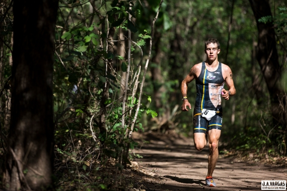 Mauricio Mendez running towards us on a natural surface trail in the forest at Playa Conchal Costa Rica.