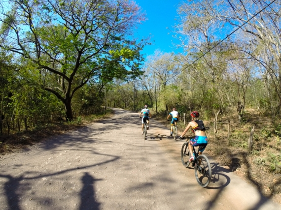Rom Akerson, Emma Garrard, and Josiah Middaugh riding on a wide dirt trail in Costa Rica.
