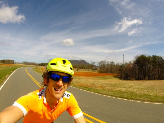 Alex Modestou riding on the road in blaze orange Pearl Izumi jersey and bright yellow Giro helmet.