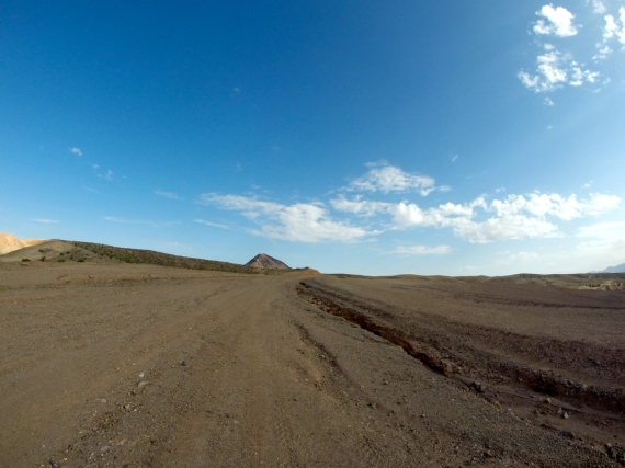 long expanse of flat desert ahead with small hill poking up at horizon in the distance.