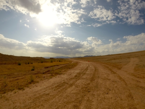Wide open dirt path in the desert, curving into horizon. Bright sun showing through the clouds in the light blue sky.