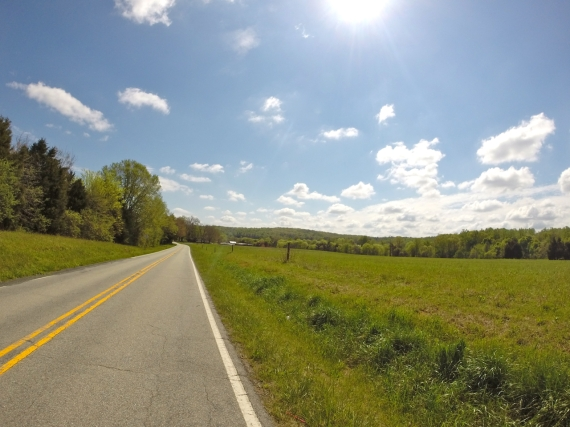 Two-lane country road, no traffic. Green farm field on the right.