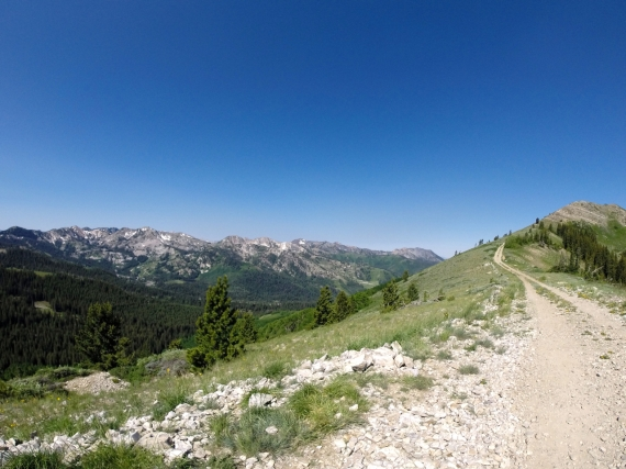 Wasatch Crest loose dirt trail winding around the mountain, overlook of mountains in the distance and clear blue sky